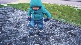 Vår lura spring ner trottoaren, gräset, den smältande snön och nedgångarna till jordningen långsam rörelse arkivfilmer