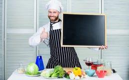 Vår skola är den bästa mannen som visar upp tummar med det tomma brädet Utbildning av matlagning- och matförberedelsen högsta koc royaltyfri bild