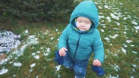 Vår Steadicam skott av ungen som kör ner trottoaren, gräset och den smältande snön långsam rörelse stock video