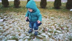 Vår Steadicam skott av ungen som kör ner trottoaren, gräset och den smältande snön långsam rörelse arkivfilmer