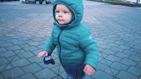 Vår Steadicam skott av ungen som kör ner trottoaren, gräset och den smältande snön långsam rörelse lager videofilmer