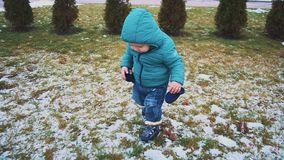 Vår unge som kör ner trottoaren, gräset och den smältande snön stock video