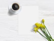 Vår utformat materielfoto Kvinnlig modell med den påskliljablommor, pingstliljan, listan av papper och koppen kaffe sjaskigt Royaltyfria Foton
