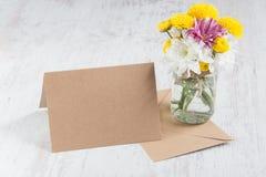 Vårblommabukett i en krusvas med kortanmärkningen och kuvert på en vit wood lantlig bakgrund Arkivbilder