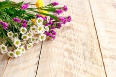 Vårblommor och kamomillar på trätabellen fotografering för bildbyråer