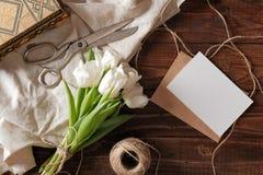 Vårbuketten av vita tulpanblommor, det tomma pappers- kortet, sax, tvinnar på det lantliga träskrivbordet Kvinnors dagsammansättn fotografering för bildbyråer