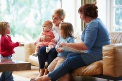 Vård- besökare som talar till modern med unga barn arkivbilder