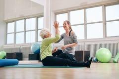 Vård- framgång för lycklig fröjd för äldre kvinna med hennes instruktör royaltyfri foto