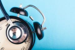 Vård- och medicinskt begrepp, ringklocka och stetoskop på blå bakgrund royaltyfri fotografi