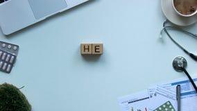Vård- ord som komponeras av kuber på tabellen, hållande leksakhjärta för doktor, stopp-rörelse lager videofilmer