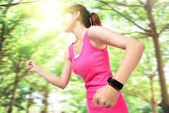 Vård- sportkvinna som bär den smarta klockan Arkivbild