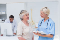 Vårda att diskutera med patienten medan doktorn som använder datoren arkivfoto