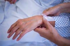 Vårda att fästa iv-droppande på handen för patient s royaltyfria bilder