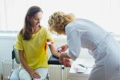Vårda att förbereda sig att göra en injektion för att ta för blod medicinskt prov Arkivfoton