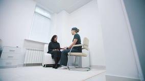 Vårda att fråga häftet av en patient på ett sjukhusmottagande lager videofilmer