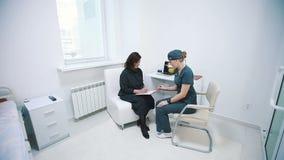 Vårda att fråga häftet av en patient på ett sjukhusmottagande arkivfilmer