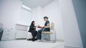 Vårda att fråga häftet av en patient på ett sjukhusmottagande stock video