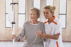 Vårda att gå bredvid en patient med droppdroppande arkivbilder
