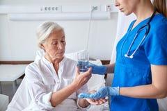 Vårda att ge medicin till den höga kvinnan på sjukhuset Royaltyfri Bild