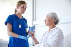 Vårda att ge medicin till den höga kvinnan på sjukhuset Arkivbild