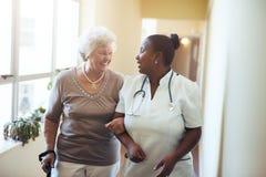 Vårda att hjälpa den höga kvinnan på sjukvårdhomeSeniorkvinnan som går i vårdhemmet som stöttas av en anhörigvårdare Sjukskötersk Royaltyfri Bild