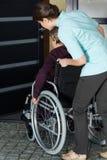 Vårda att hjälpa en rörelsehindrad kvinna att skriva in huset arkivbild