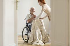 Vårda att ta omsorg av den lyckliga äldre mannen i en rullstol i hans ho royaltyfri foto