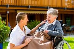 Vårda den driftiga höga kvinnan i rullstol går på Royaltyfri Foto