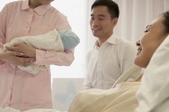 Vårda hållande nyfött behandla som ett barn i sjukhuset med modern som ligger på sängen och fadern bredvid henne Royaltyfri Foto