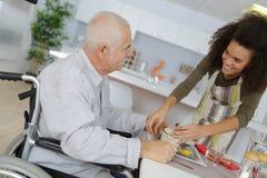 Vårda i hemmet för gammalt folk som ger den tålmodiga matställen arkivbilder
