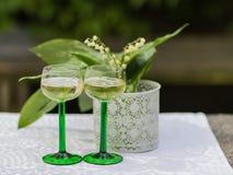 Vårdag med liljekonvaljen och två exponeringsglas av vitt vin royaltyfria foton