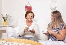 Vårdare som har en kopp te med en äldre kvinna Royaltyfri Bild