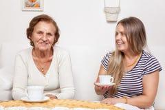 Vårdare som har en kopp te med en äldre kvinna Arkivfoto