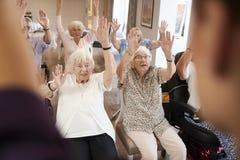 Vårdare som leder gruppen av pensionärer i konditiongrupp i avgånghem royaltyfri bild