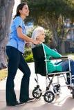 Vårdare som skjuter den höga kvinnan i rullstol Arkivfoton