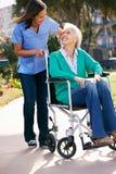 Vårdare som skjuter den höga kvinnan i rullstol Royaltyfria Bilder
