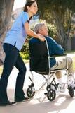 Vårdare som skjuter den höga mannen i rullstol Royaltyfria Bilder