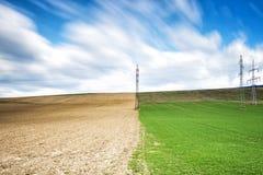 Vårfält med elektriska pelare Fotografering för Bildbyråer