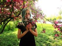 Vårflickan med grönt hår står under det blommande körsbärsröda trädet, som blommar royaltyfri foto