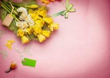 Vårhälsningblommor samlar ihop med den tomma etiketten och garnering Pingstlilja på pastellfärgad bakgrund Arkivbilder