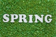 vårinskrift i vita bokstäver på en grön bakgrund av små kiselstenar, säsongsbetonad abstraktion royaltyfria foton