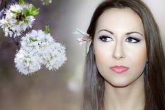 Vårkvinnan på en bakgrund med våren blommar, den vita blomningen Arkivfoton