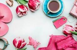 Vårkvinnors workspace med tulpan blommar, rosa färgkläder och skor, etiketter och kaffekoppen, bästa sikt Royaltyfria Bilder