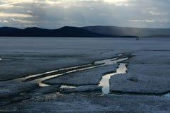 Vårlandskap med isdriva på sjön arkivbild