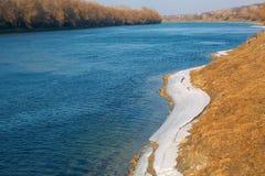 Vårlandskap med snö på flodstranden Fotografering för Bildbyråer