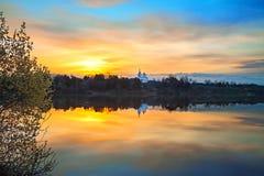 Vårlandskap med soluppgång över vatten Arkivbild
