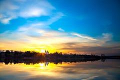 Vårlandskap med soluppgång över vatten Arkivfoton