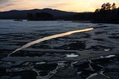 Vårlandskap på en sjö med smältande kuster i aftonen arkivfoto