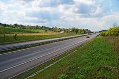 Vårlandslandskap med en huvudväg Arkivbild