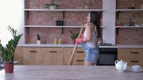 Vårlokalvård och att le flickan i grov bomullstvilloveraller och handskar har lyckligt gyckel i kök med en kvast- och rengöri